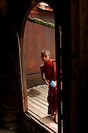 Novice monk looking inside Shwe Yan Pya monastery