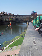 Tourists looking at the Ponte Vecchio or 'Old Bridge', a Medieval stone bridge over the Arno River in Florence, Italy. It is a closed-spandrel segmental arch bridge. The bridge is famous for having shops built along it, originally butchers, but now souvenir shops, jewellers, and art dealers reside in the shops.