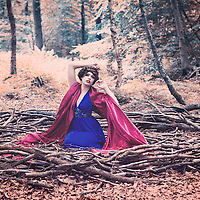 Young woman with brunette hair in blue dress and a red stole sitting in a large bird nest alone in the forest like a fairytale