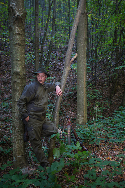 Romanian forester leaning at a Common beech (Fagus sylvatica) trunk at his shooting stand during a driving hunt for Wild boar (Sus scrofa). Mehadia, Caras Severin, Romania.