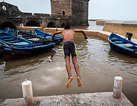 ESSAOUIRA, MOROCCO - CIRCA MAY 2018:  Kids jumping from the jetty over the port of Essaouria and the famous Castelo Real of Mogador.