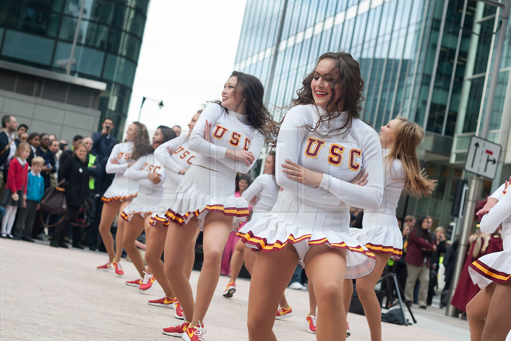 © licensed to London News Pictures. London, UK 17/05/2012. Cheerleaders perfoming in Canary Wharf as the Trojan Marching Band of the University of Southern California comes to Canary Wharf for the first time performance in Canada Square Park, this evening (17/05/12). Photo credit: Tolga Akmen/LNP
