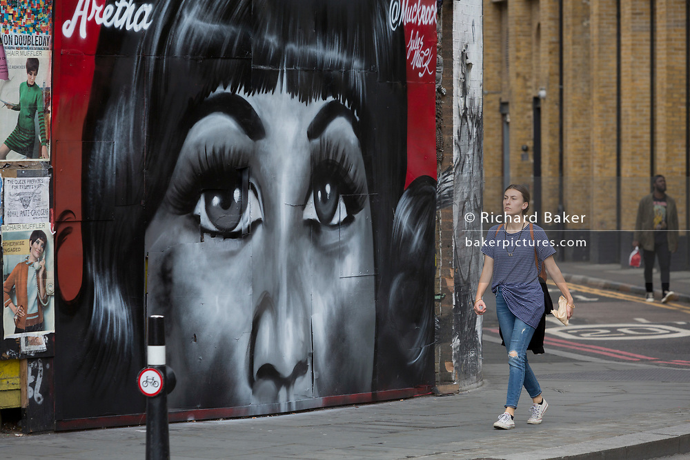 A Londoner walks past a recent mural in Shoreditch (by artist Jules Muck) of Soul Queen Aretha Franklin who died a few days earlier, on 20th August 2018, in London, England.