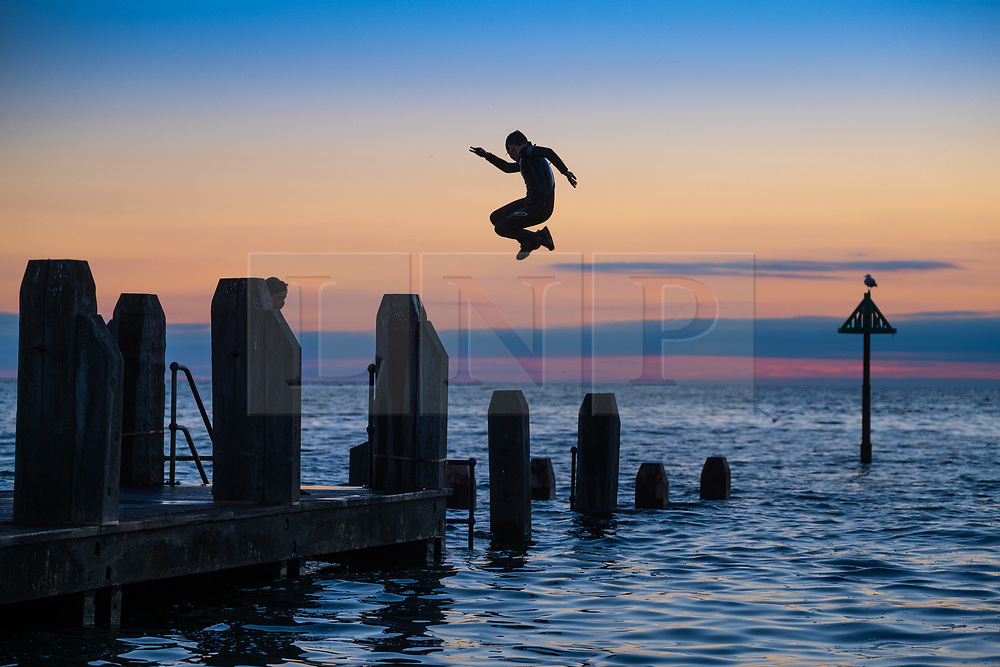 © Licensed to London News Pictures<br /> 05/07/2019. Aberystwyth, UK. In the fading light at the end of a day of hot sunshine, youngsters cool off by jumping acrobatically into the sea off the wooden jetty in Aberystwyth on the Cardigan Bay coast, west Wales. Photo credit: Keith Morris/LNP