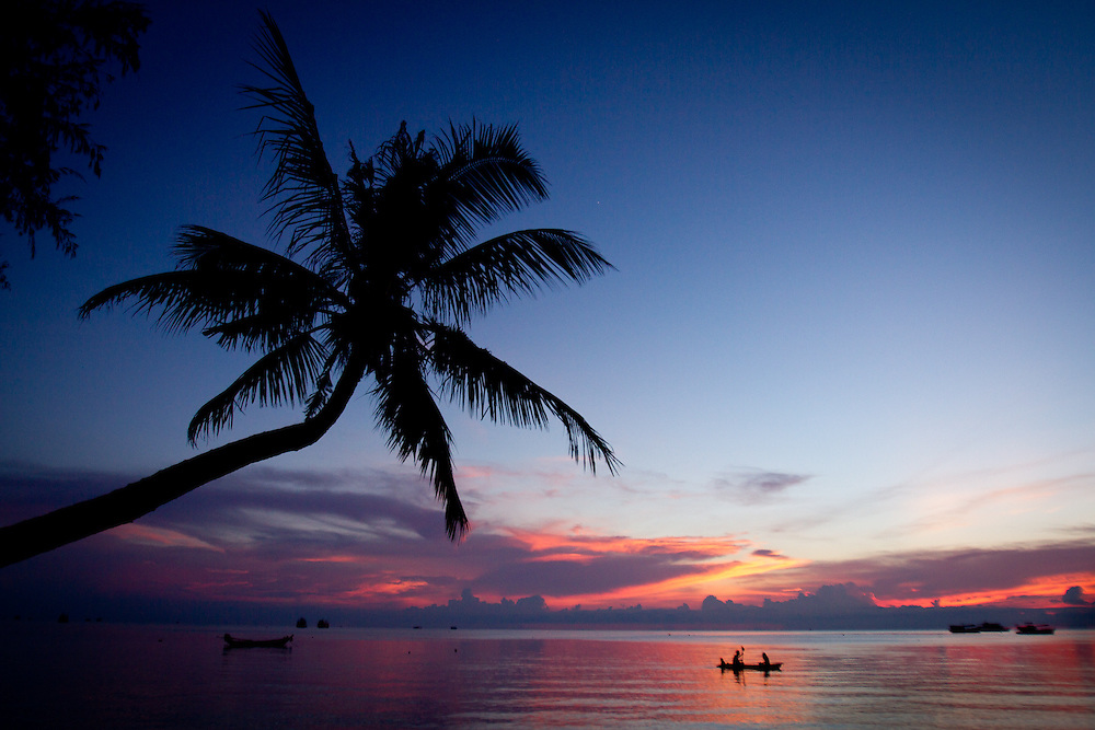 Two people paddle a kayak as the sun sets on tropical Koh Tao island, Thailand.