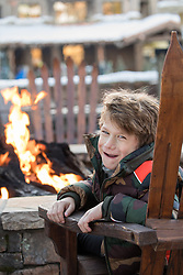 little boy smiling while sitting by a fire pit at a ski lodge