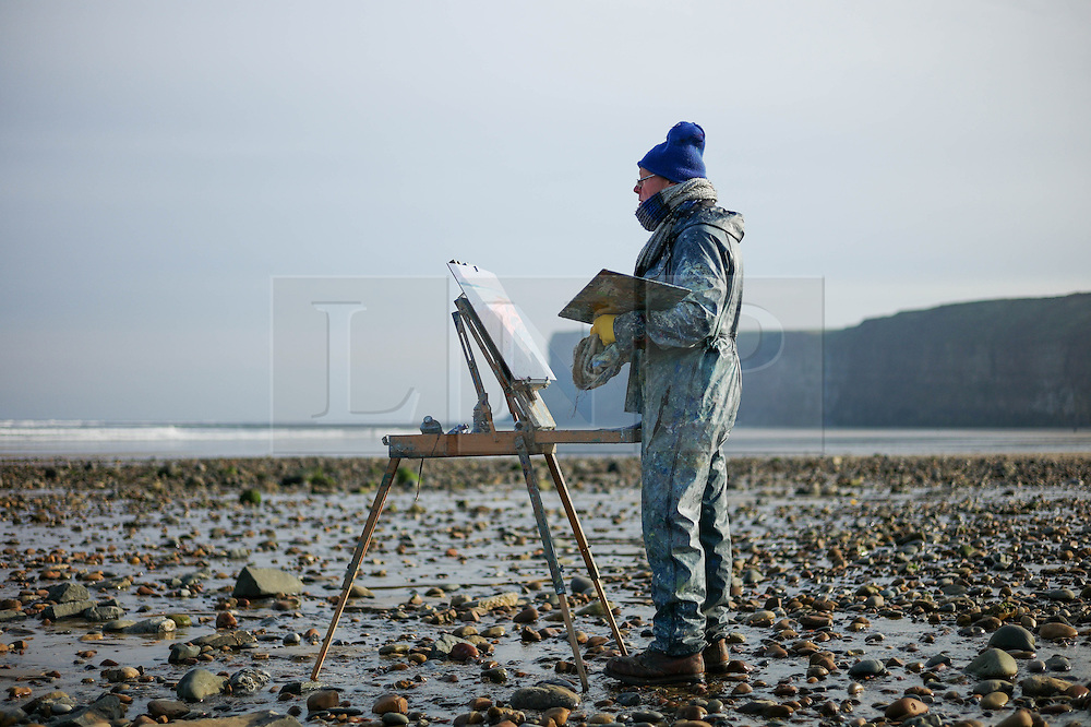 © Licensed to London News Pictures. <br /> 06/11//2014. <br /> <br /> Saltburn, United Kingdom<br /> <br /> Piers Browne, an artist from Wensleydale stands with his paints and easel on the beach at Saltburn by the Sea in Cleveland as he paints on a cold sunny morning on the east coast.<br /> <br /> Photo credit : Ian Forsyth/LNP