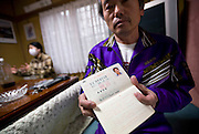Former nuclear power plant worker Yuji Watanabe shows a company record book at his home in Minami-Soma, Fukushima Prefecture, Japan on 30 March, 2011.  Photographer: Robert Gilhooly