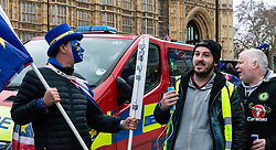 Pro-Brexit campaigner James Goddard in his yellow jacket that copies the French 'Gilet June' imagery once again visits and attempts to disrupt Steve Bray's (left) SODEM anti-Brexit protest the day after he was seen harassing former cabinet minister Anna Soubry. Westminster, London, December 20 2018.