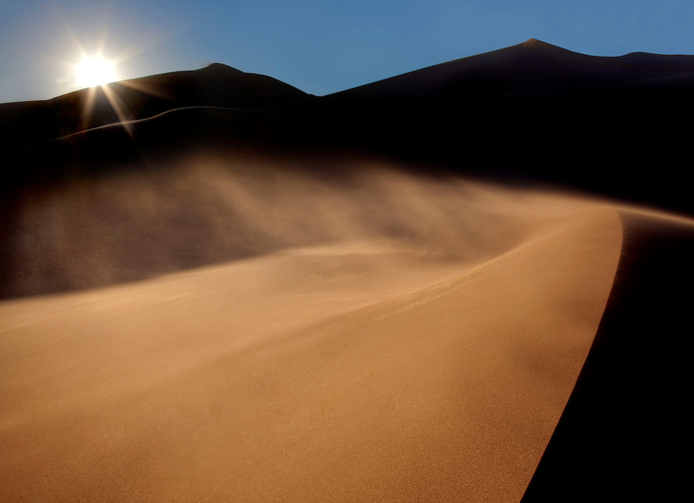 The sun sets over distant dunes during a sandstorm, while the wind lifts a plume of sand off or a near dune, Great Sand Dunes National Park, USA.