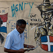 SANTO DOMINGO, DOMINICAN REPUBLIC-DECEMBER 3, 2014: A man slowly strolls reading the daily newspaper past a mural depicting a Dominican patriot, Juan Pablo Duarte, left, and a traditional merengue musician playing a tambour drum in Santo Domingo's Zona Colonial (Colonial Zone). Story on tourism to the Caribbean Island.  (Photo by Angel Valentin/Getty Images for Der Spiegel)
