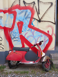 Scooter parked beside house wall covered in graffiti in Prenzlauer Berg district of Berlin Germany
