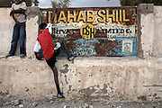 Boys climb on an advertising board in Hargeisa, Somaliland, on Sunday, July 22, 2007. Dahadshil is the major money transfer operater in Somaliland and the country is heavily reliant on money send home by the diaspora, estimated to be $300 million per year..