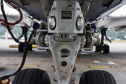 A close-up detail of a Boeing 747 main nosewheel and landing lights during the aircraft's turnaround at Heathrow Airport.