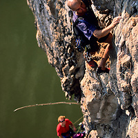 Jose Pereyra climbs an unnamed 5.10 with partner Will Hair high above the Nam Ou River, Ban Pak Ou, Luang Phrabang, Laos