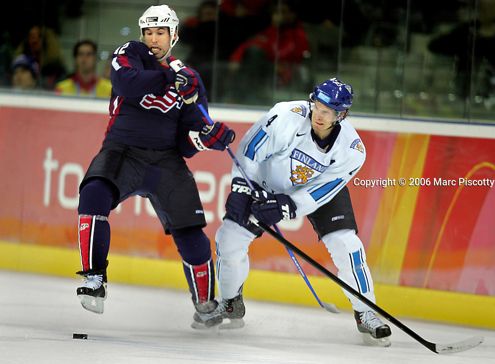 Team Finland's Kimmo Timonen (#4) grabs the stick of Team U.S.A.'s Brian Rolston (#12) as the two battle for a loose puck during the second period of their Quarterfinal game at the Palasport Olimpico in Turin, Italy on Wednesday February 22, 2006. The winner advances in the tournament and the loser is finished for the 2006 Winter Olympics. The U.S. Hockey Team lost the game 3-4 and is out of the playoffs..(Photo by Marc Piscotty / © 2006)