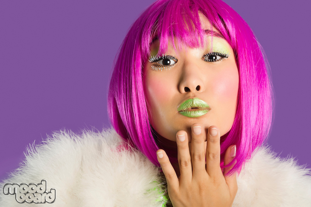 Portrait of young funky woman in pink wig blowing kiss over purple background