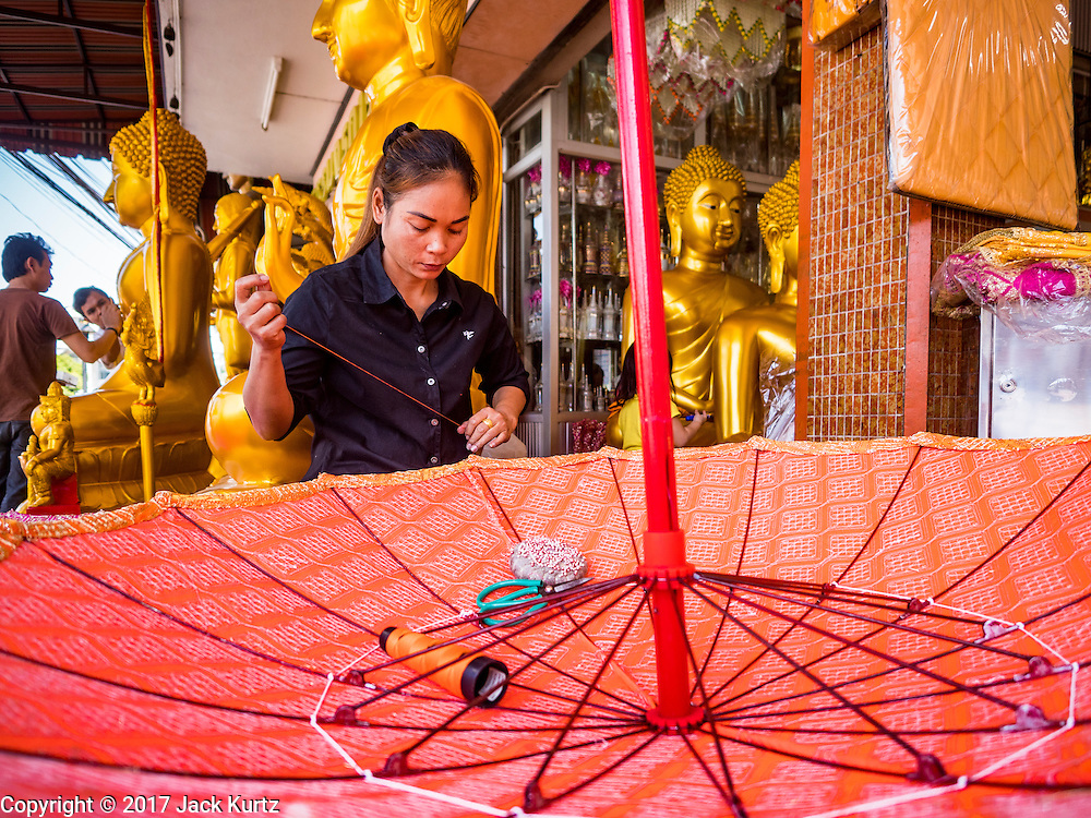 01 FEBRUARY 2017 - BANGKOK, THAILAND: A woman works on a large traditional parasol at a shop that makes and sells Buddhist paraphernalia in Bangkok. The umbrellas are used as parasols to keep the sun off important Buddha statues and at formal events. In Thai culture, the parasols were used to provide shade for members of the royal family or representatives of the royal family.     PHOTO BY JACK KURTZ