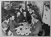 Journalists from Le Canard Enchaine playing cards at the Cafe du Cadran in Paris, c. 1930, photograph, with (right) Maurice Marechal and his wife Jeanne Marechal, (opposite) Henri Monnier and (centre) Jules Rivet, copyeditor of the newspaper. The photograph is in the collection of the Archives du Canard Enchaine. Le Canard Enchaine is a satirical weekly newspaper, founded in 1915 during the First World War by Maurice Marechal, Jeanne Marechal and H P Gassier. It features investigative journalism, political cartoons, business and political leaks and bogus interviews. In 2015 the newspaper celebrated its 100th anniversary. Picture by Manuel Cohen