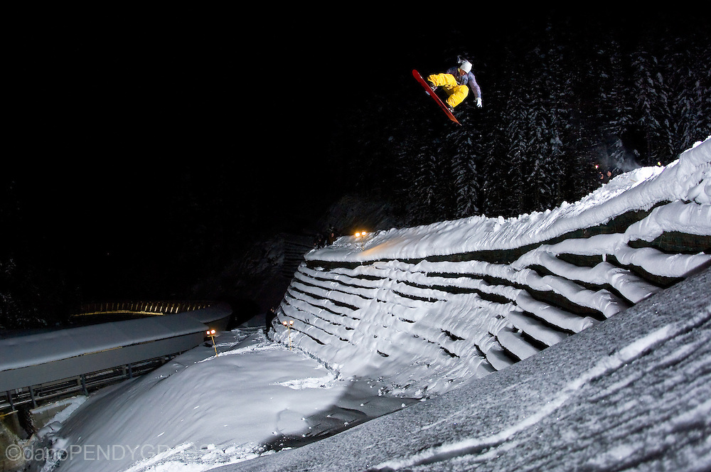 Professional Snowboarder Chris Wimbles launches a man made cliff at night, near Whistler, British Columbia.