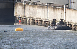 © Licensed to London News Pictures. 12/02/2018. London, UK. Members of the Royal Navy Bomb Disposal Team sit in a boat near the location of the unexploded bomb next to London City Airport which remains closed. A World War II era bomb was found in The River Thames during routine work on nearby King V Dock. Police have evacuated nearby residents, closed the airport and set up a 214-metre exclusion zone. Photo credit: Peter Macdiarmid/LNP
