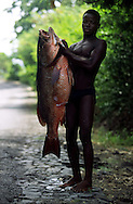 Fisherman selling a huge fish on the roadside in tyhe northern coast of Sao Tome island.