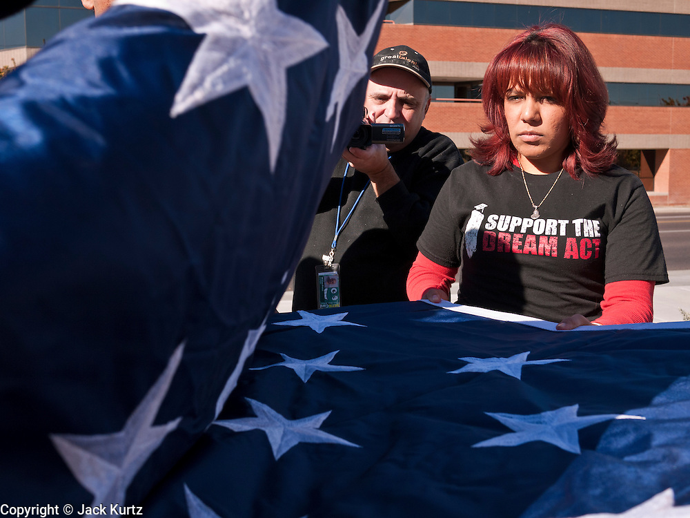 "07 DECEMBER 2010 - PHOENIX, AZ:  YADIRA GAROA and other supporters of the DREAM Act fold up an American flag after picketing the offices of US Sen. John McCain in Phoenix Tuesday. Dolores Huerta, who started working in the civil rights movement in the 1960's, threw her support behind students fasting on behalf of the DREAM Act in front of Sen. John McCain's office Tuesday. The student picked McCain's office because he used to support the DREAM Act. They hope that the US Senate will pass the DREAM Act during its ""lame duck"" session. The Senate debated and defeated similar legislation just before the November general election.   PHOTO BY JACK KURTZ"