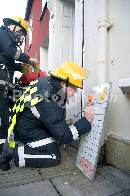 Fire brigade Entry Control Officer recording details of officers attending incident on  board outside house on fire