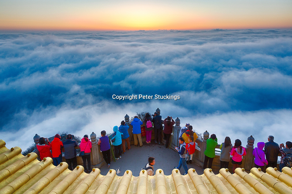 Tourists gather to see sunrise at the Golden Summit Temple at the peak of Emeishan, Sichuan province