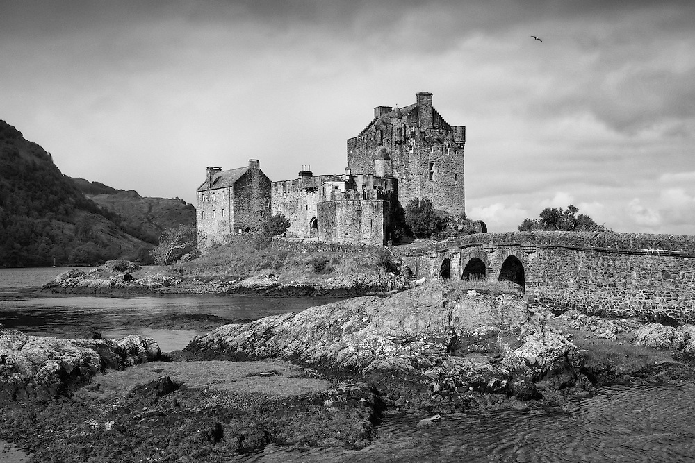 Eilean Donan offers one of the most iconic images of Scotland. It is situated on an island at the point where three great sea lochs meet, and surrounded by some majestic scenery.<br /> <br /> First inhabited around the 6th century, the first fortified castle was built in the mid 13th century and stood guard over the lands of Kintail. Since then, at least four different versions of the castle have been built and re-built as the feudal history of Scotland unfolded through the centuries.<br /> <br /> Partially destroyed in a Jacobite uprising in 1719, Eilean Donan lay in ruins for the best part of 200 years until Lieutenant Colonel John MacRae-Gilstrap bought the island in 1911 and proceeded to restore the castle to its former glory. After 20 years of toil and labour the castle was re-opened in 1932.<br /> <br /> This photograph is a monochromatic version of the view of Eilean Donan Castle close to the brifge gatehouse. The photograph can be purchased as print, mounted print in frames, canvas or aluminum or as a digital file.