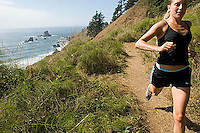 Young woman trail running in Ecola State Park. Cannon Beach, OR