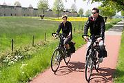 Een man en vrouw fietsen voorbij de zogenaamde kasteelwoningen aan de rand van Zevenaar, een plaatsje in de streek De Liemers in het oosten van Nederland. De woningen zijn zo ontworpen dat ze gelijk een geluidswal zijn voor de achterliggende wijk.<br /> <br /> A man and woman cycle past the so-called castle houses on the edge of Zevenaar, a town in the region the Liemers in the east of the Netherlands. The houses are designed to be like a sound barrier for the underlying district.