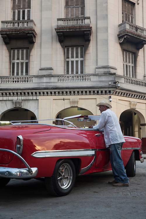 Taxi driver waiting for clients by his car, and old American convertible, at Parque Central in Havana, Cuba.