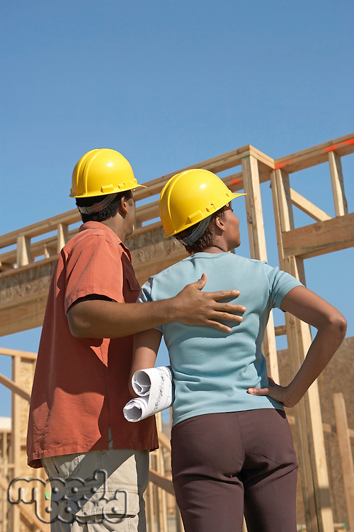Couple in hard hats on building site back view