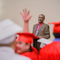 New Life Learning Center executive director Benson Ndolo watches as his students prepare for their graduation ceremony Friday at Lighthouse Church in Gallup.