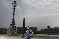 Cyclist on bicycle standing by river embankment London England