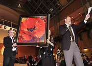 "A 36"" x 36"" Master Edition of Simon Bull's ""Lady in Red"" is displayed to the crowd as Auctioneer Mike Baker, from Greenville talks at the 2007 Wellness Connection Red Dress Gala, at the Schuster Performing Arts Center in Dayton, Saturday night, May 5th."