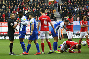 Referee Stephen Martin takes Wigan Athletic defender Cheyenne Dunkley (22) to the side to show him the yellow card for the tackle on Middlesbrough midfielder Lewis Wing (26) during the EFL Sky Bet Championship match between Wigan Athletic and Middlesbrough at the DW Stadium, Wigan, England on 2 March 2019.