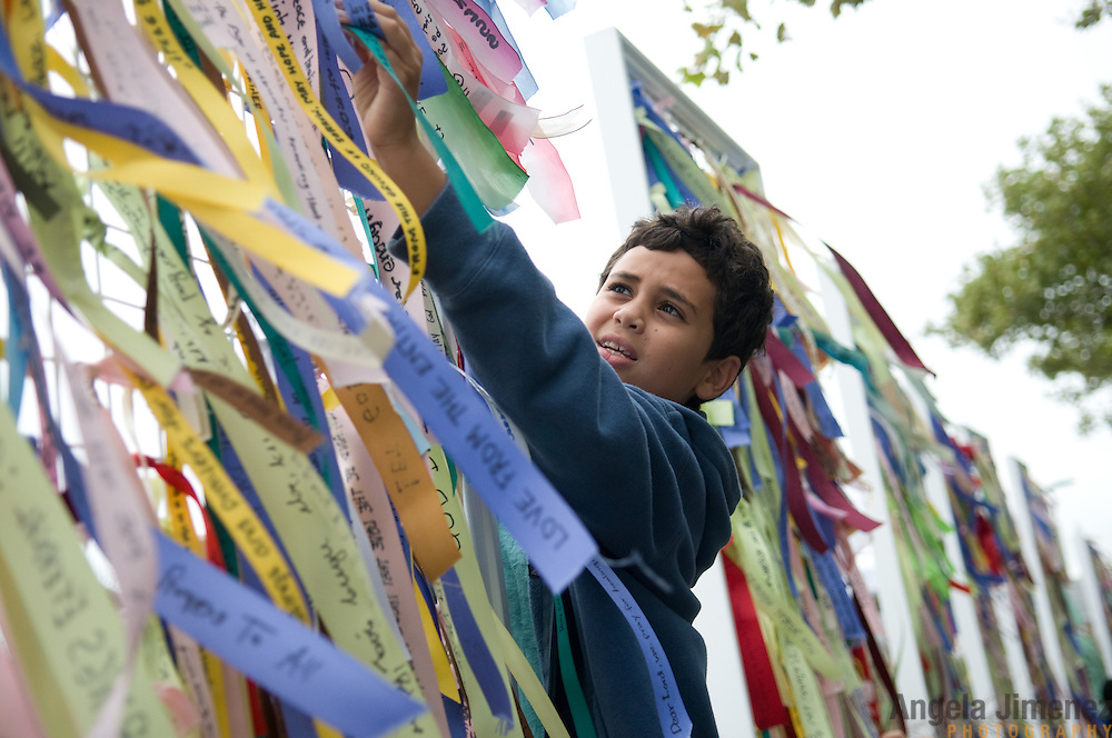 People participate in Prepare New York's Ribbons of Hope public art project on the tenth anniversary of the 9-11 terrorist attacks in Battery Park in New York City on September 11, 2011. Ribbons inscribed with personal messages were tied to display panels which stood in the Park over the weekend. <br /> <br /> <br /> Prepare New York is a coalition of New York-based interfaith organizations, including Auburn Seminary and its Center for Multifaith Education, Interfaith Center of New York, Intersections International, Odyssey Networks, Quest, and Tanenbaum and its Religion and Diversity Education Program, who have joined together to &quot;help create a city-wide climate that promotes healing and reconciliation&quot; in anticipation of the tenth anniversary of 9/11. September 11th Families for Peaceful Tomorrows, 9/11 Community for Common Ground Initiative, and Abraham's Path are serving as advisers to the multifaith organizations.<br /> <br /> Photographed by Angela Jimenez for Prepare New York<br /> www.angelajimenezphotography.com