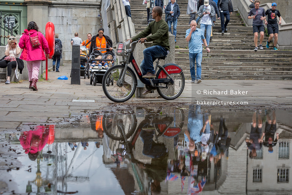 After heavy rainfall the day before, a cylist and other people are reflected in a puddle on the Albert Embankment on the Lambeth side of Westminster Bridge, on 11th June 2019, in London, England.