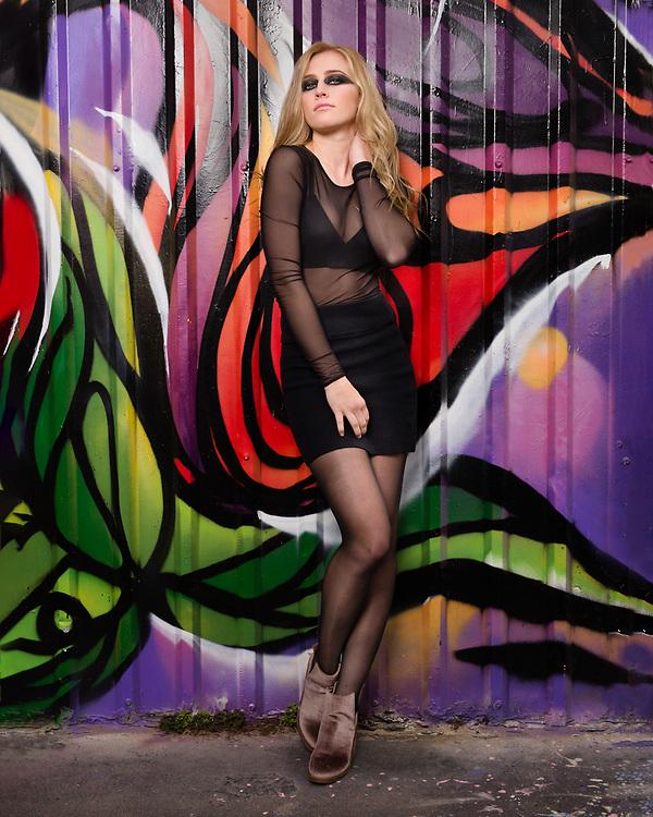 Houston Model and actress Savannah O'Hara poses in club attire in front of vivid graffitti art wall.