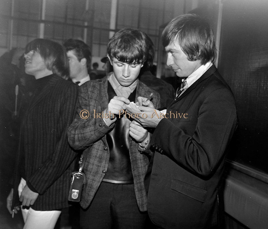 .Historic Irish Photographs To Feature in New Rolling Stones DVD Release...Fourteen never before seen photographs of The Rolling Stones, which were shot in Dublin in 1965, are to feature prominently in a new DVD and Blu-Ray, which is being released on November 2...The Rolling Stones Charlie is My Darling - Ireland 1965 film has its world premiere in New York on Saturday, September 29, and will then receive an international release. (see details below)..Picture Caption..The Rolling Stones Charlie is my Darling - Ireland 1965 -.Charlie Watts of The Rolling Stones sighns an autograph for a young fan, while bandmate Brian Jones sees something interesting at Dublin Airport, before thier concert in the Adelphi Theatre, Middle Abbey Street, Dublin. This was the band's second Irish tour of 1965...The DVD of the film will be released on November 2 and the film box set and 42-page Collector's Edition hardcover book includes 14 never before seen images that have been painstakingly restored by the Irish Photo Archive. The original images were shot by Lensmen Photographic Agency, which was established in 1952 and is still a prominent Dublin-based photography company..The images were taken on September 3 1965, when the movie was shot on a quick weekend tour of Ireland just weeks after ?(I Can't Get No) Satisfaction? hit No. 1 on the charts and became the international anthem for an entire generation. The images feature the band at Dublin Airport, performing at the Adelphi, backstage and at Connolly Station. The Rolling Stones photographs will be on public display in the mezzanine area of Terminal 1 at Dublin Airport from November...The Stones photos, were recently discovered when the Irish Photo Archive was being catalogued. The archive is a treasure trove of more than two million photos, including many other celebrity photos that have never been published..The Rolling Stones images are online at www.irishphotoarchive.ie Please credit www.irishphotoarchive.ie published any of our