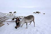 A Nenets boy plays with a reindeer outside the family chum. These skills learned during play will come in handy in adulthood.