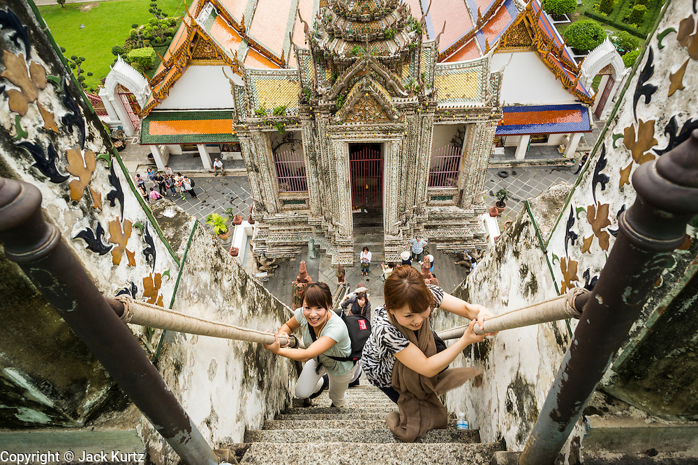 "23 SEPTEMBER 2013 - BANGKOK, THAILAND: Tourists climb the stairs of the famous central chedi at Wat Arun on the last day the stupa would be open for climbing. The full name of the temple is Wat Arunratchawararam Ratchaworamahavihara. The outstanding feature of Wat Arun is its central prang (Khmer-style tower). The world-famous stupa, known locally as Phra Prang Wat Arun, will be closed for three years to undergo repairs and renovation along with other structures in the temple compound. This will be the biggest repair and renovation work on the stupa in the last 14 years. In the past, even while large-scale work was being done, the stupa used to remain open to tourists. It may be named ""Temple of the Dawn"" because the first light of morning reflects off the surface of the temple with a pearly iridescence. The height is reported by different sources as between 66,80 meters and 86 meters. The corners are marked by 4 smaller satellite prangs. The temple was built in the days of Thailand's ancient capital of Ayutthaya and originally known as Wat Makok (The Olive Temple). King Rama IV gave the temple the present name Wat Arunratchawararam. Wat Arun officially ordained its first westerner, an American, in 2005. The central prang symbolizes Mount Meru of the Indian cosmology. The temple's distinctive silhouette is the logo of the Tourism Authority of Thailand.           PHOTO BY JACK KURTZ"
