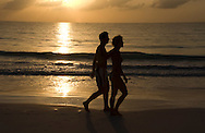 A couple walking on Pink Sands Beach at sunrise.  Harbour Island, The Bahamas