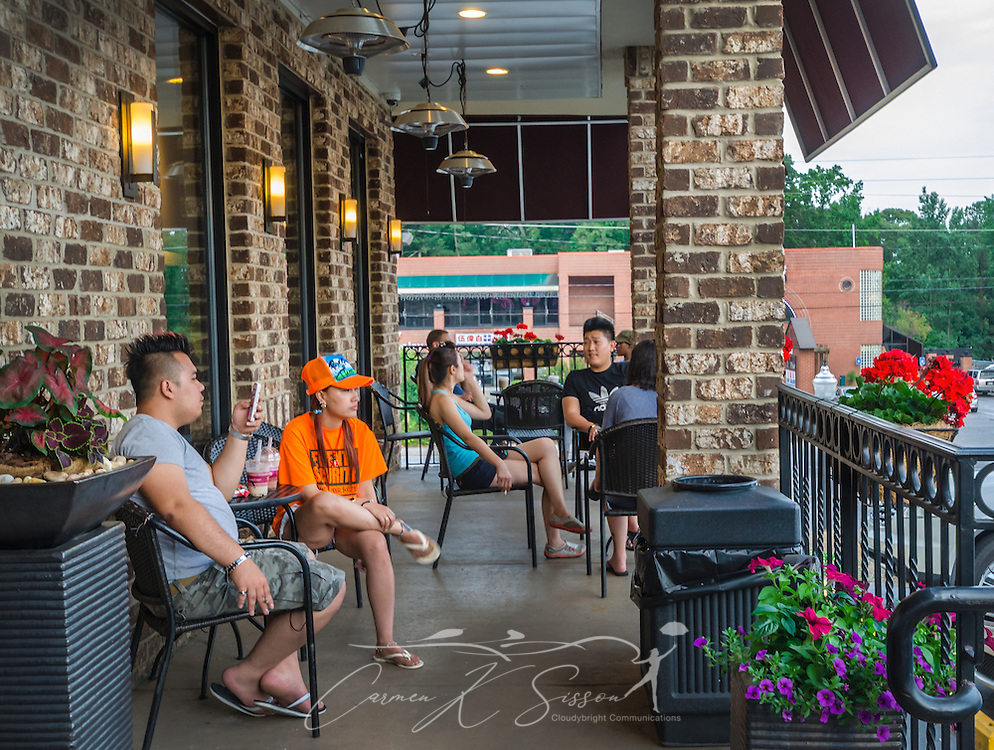 Customers socialize on the patio at Sweet Hut Bakery and Cafe, May 29, 2014, in Doraville, Georgia. Sweet Hut, a boutique bakery and bistro, opened in 2012 and caters to the international community, offering more than 200 Asian-inspired delicacies and drinks. Popular items include the Hong Kong Polo Bun and Taiwanese bubble tea. (Photo by Carmen K. Sisson/Cloudybright)
