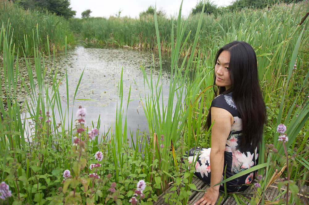 An Asian young woman wearing a silk dress with a floral pattern relaxing outdoors
