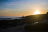 Surfer silhouetted by sunset, Santa Cruz, California
