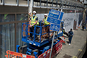 A workman wearing hi-visibility tabard and a face covering, stands as a safety lookout overlooking pedestrians walking below, during the construction of new apartments on the Walworth Road near Camberwell, on 3rd July 2020, in London, England.