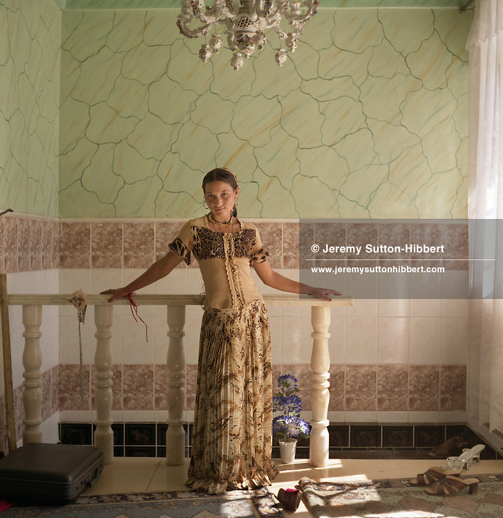 """A young, married,  Roma girl stands posing like a """"Western"""" model in the hallway of her parents home. The home is one of 100 houses built in the last 7 years with the profits of scrap metal dealing, in the village of Sintesti.."""